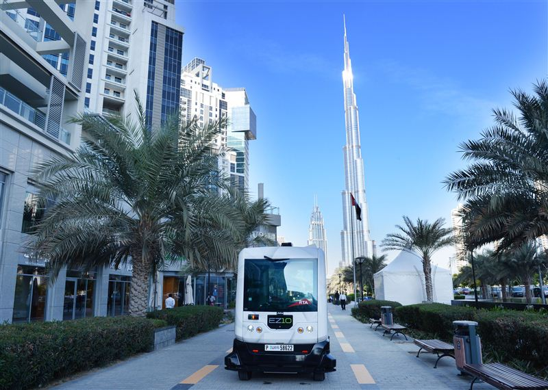 Driverless electric shuttle EZ10 against the backdrop of the towering Burj Khalifa in Dubai.
