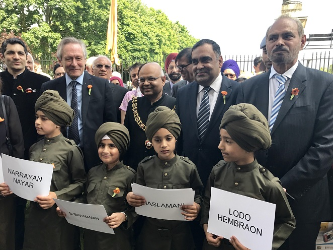 Children dressed as Labour Corps holding up names of those who served the British during World War I. High Commissioner Y K Sinha (2nd from Right) looks on.
