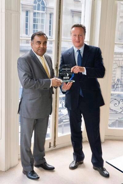 Indian High Commissioner to UK Y K Sinha presents a 'Special Recognition Award' to former British PM David Cameron.