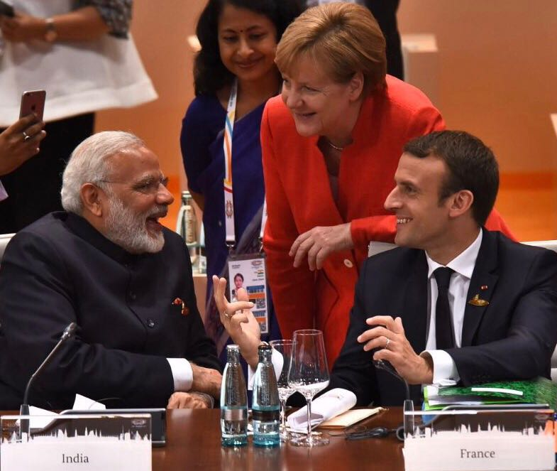 Modi (left) interacting with German Chancellor Angela Merkel (centre) and French President Emmanuel Macron during a panel discussion.