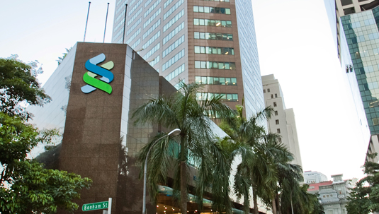 Raffles Place Office Building with Standard Chartered logo in Singapore.