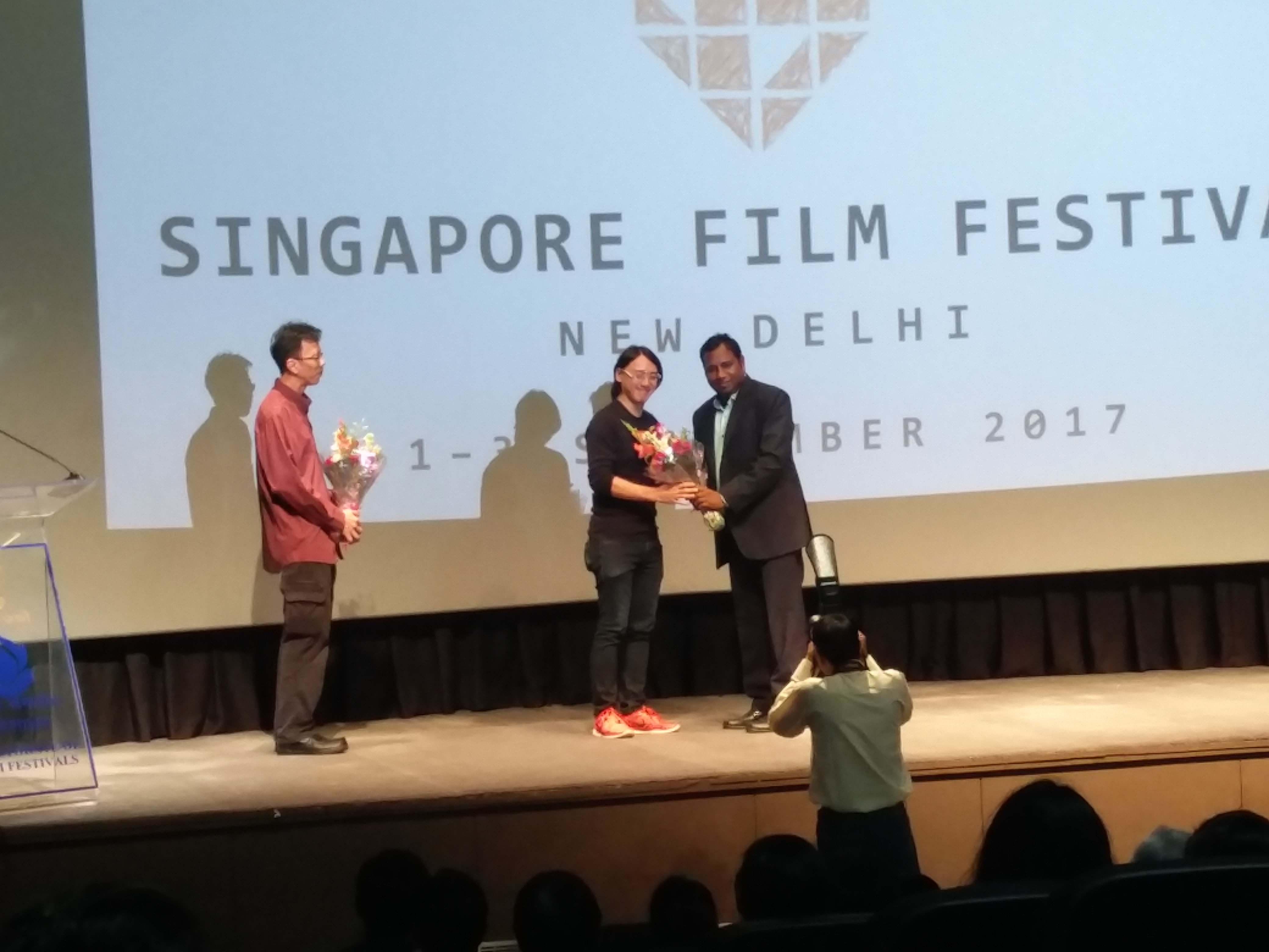 DFF director felicitating 'That Girl in a PInafore' director Yee Wei Chai, as music producer, Zennon Goh looks on.