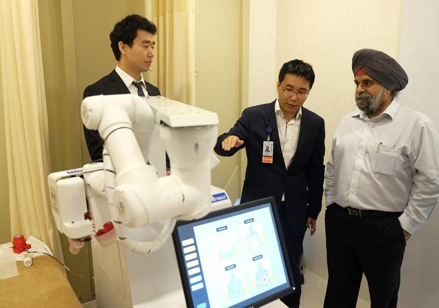 Inderjit Singh, Chairman of NTUitive, NTU's innovation and enterprise arm, gets a demo of Emma from Albert Zhang, founder of AiTreat, and NTU PhD student Liu Kai.