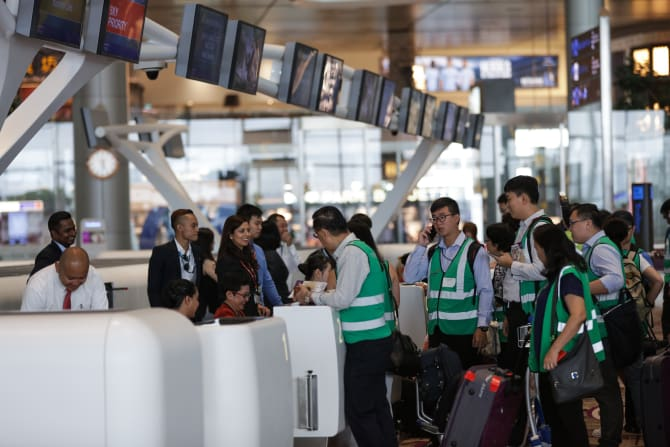 Ground handling agents attending to participants'  checking-in during the dress rehearsal at Changi Airport.