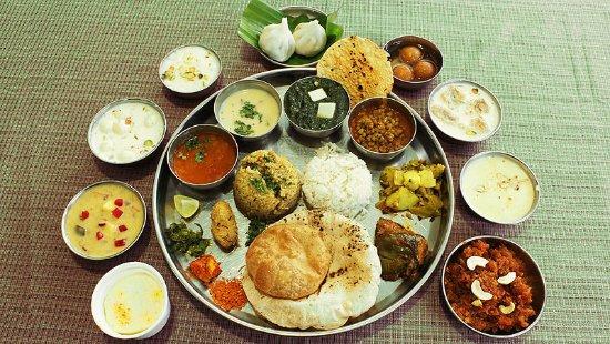 The delicious typical thali has aamras, kosimbir, bhakri roti (millet flatbread), pitla (thick chickpea flour curry), amti (spicy & tangy toor lentil), mutton Kolhapuri, sabudana vada and desserts like kheer & basundi
