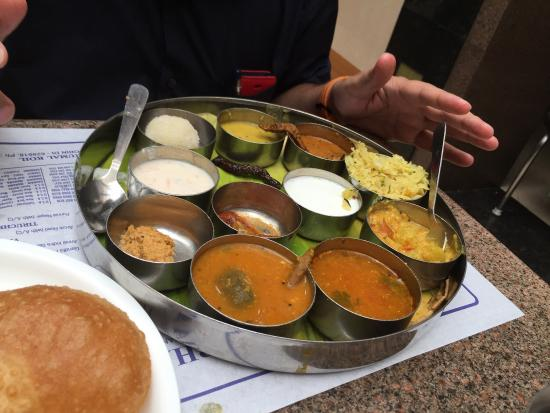 An amalgamation of flavours ranging from spicy to sweet, the thali comprises of rasam, plain rice, curd, badam payasam, sambar, poriyal (curry), kootu etc