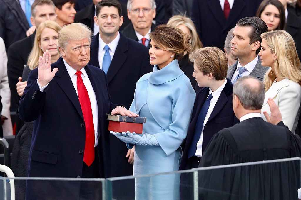 With right hand raised, Donald Trump looks at John Roberts with his back to the camera, as Melania Trump and others watch