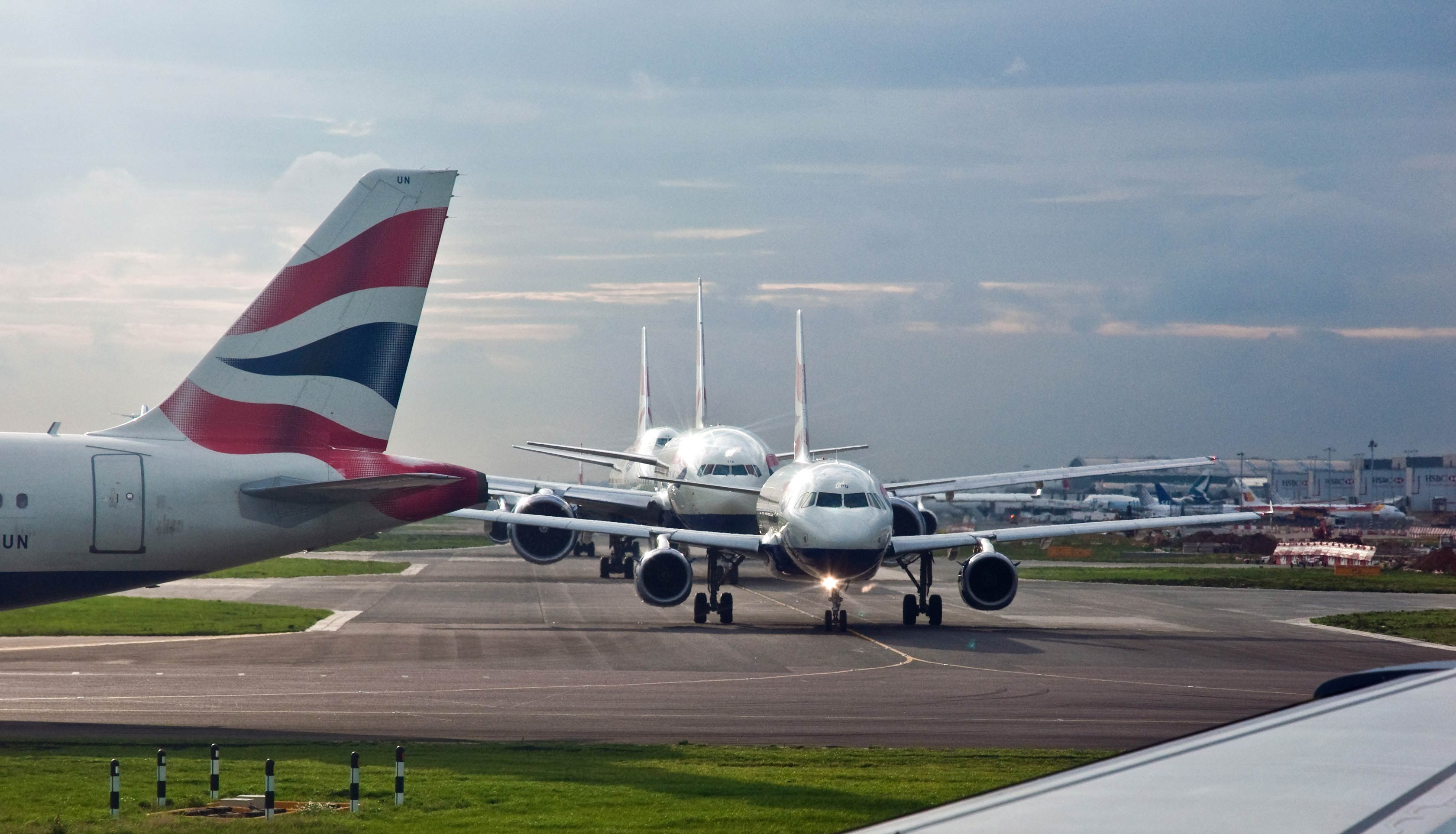 Planes lining up on a runway at Heathrow Airport.