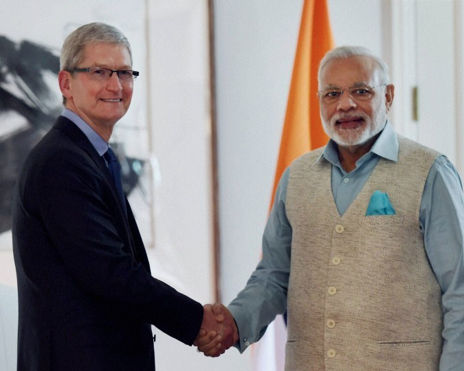 PM of India Narendra Modi, looking dapper, in a handshake with Tim Cook CEO Apple Photo courtesy: pmjandhanyojana.co.in