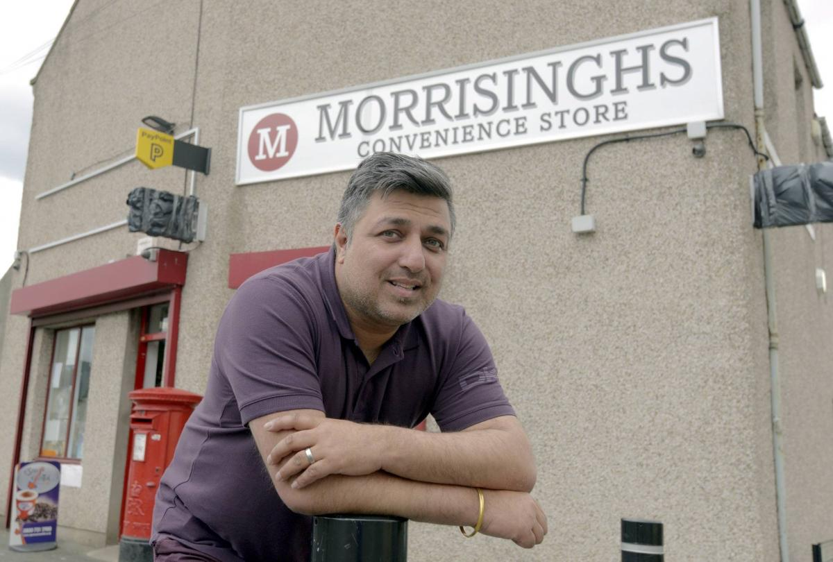 Jel Singh Nagra showing his new shop sign.