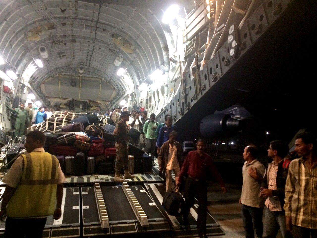 Evacuated men and women from war-torn Yemen walk out of tail-hatch of Indian Air Force transport aircraft on April 02, 2015.