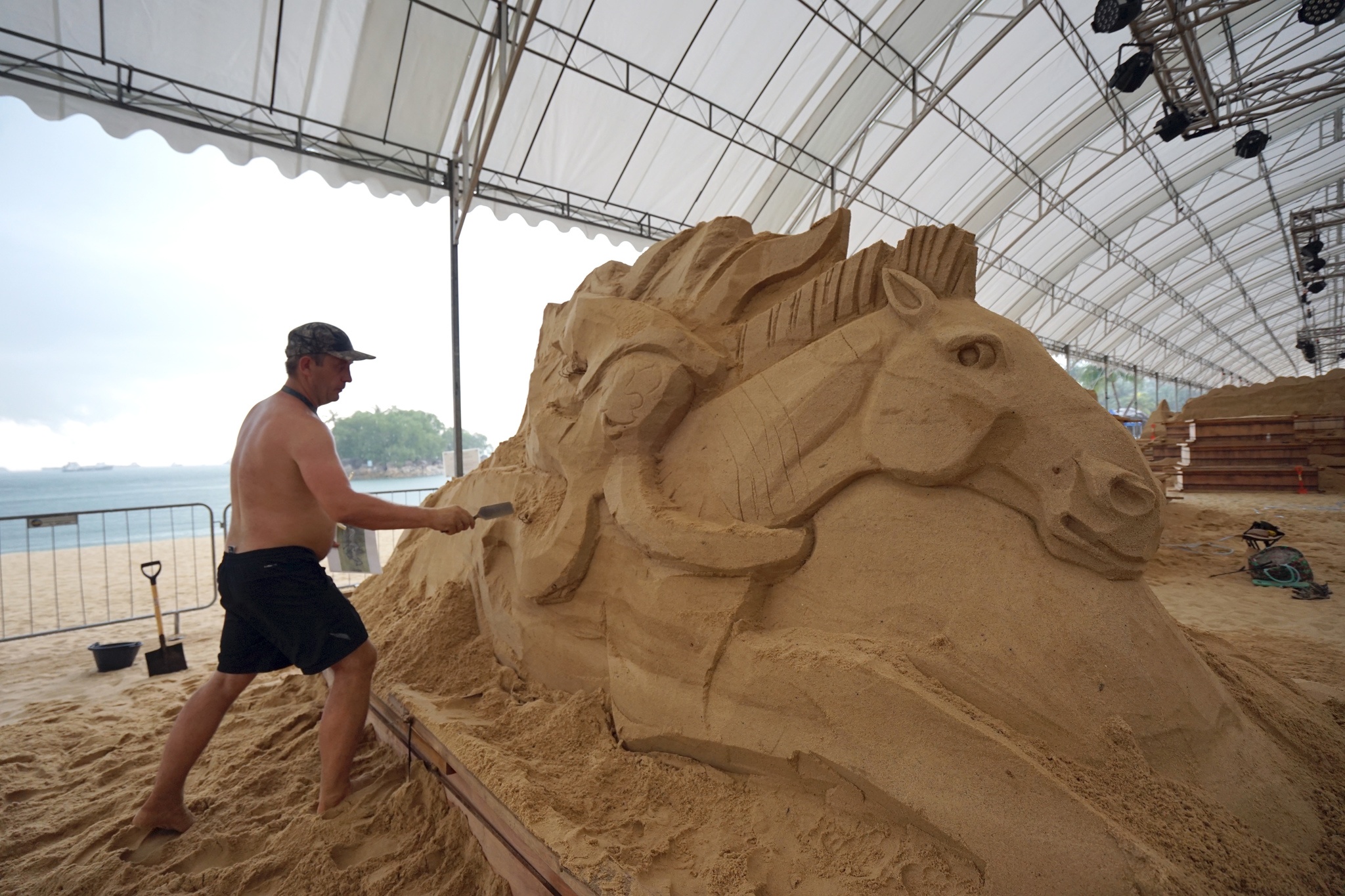 Artists giving final touches to the sand sculptor on Siloso Beach in Singapore.