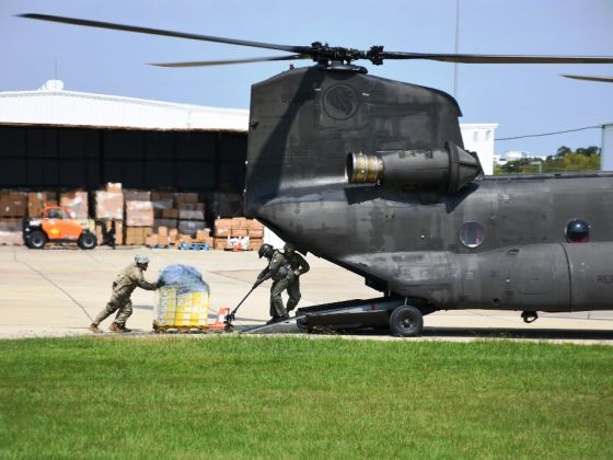 Airmen from the Republic of Singapore Air Force (RSAF) working closely with soldiers from the Texas Army National Guard (TXARNG) to load supplies onto the RSAF's CH-47 Chinook helicopter
