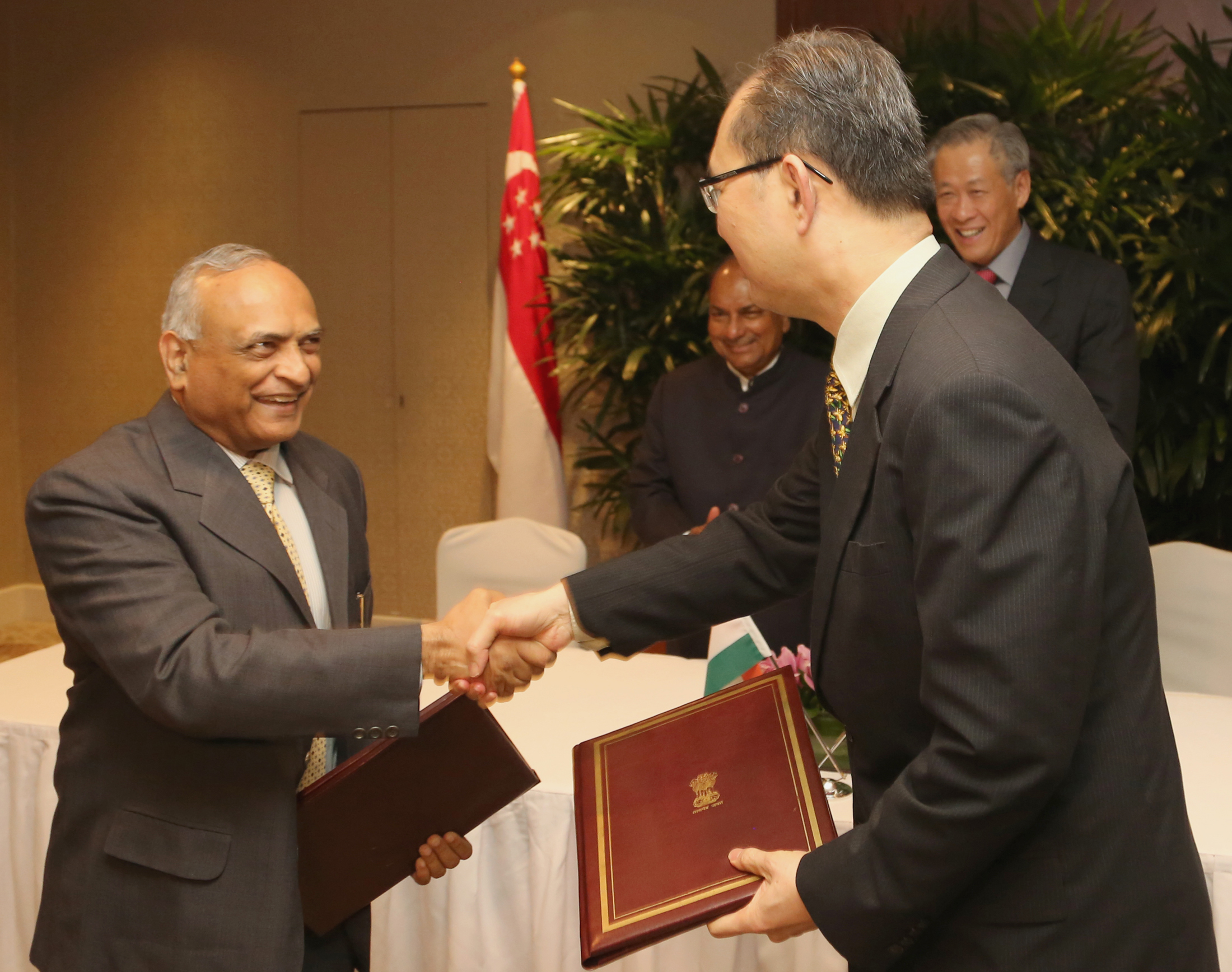 The Indian Defence Secretary, Radha Krishna Mathur and Singaporean Permanent Secretary of Defence, Chiang Chie Foo exchanging the signed documents of an agreement to extend the use of training and exercise facilities in India by the Singapore Army for a further period of five years from August this year, in the presence of the Defence Minister, A. K. Antony and his Singaporean counterpart Dr. Ng Eng Hen, in Singapore on June 03, 2013.