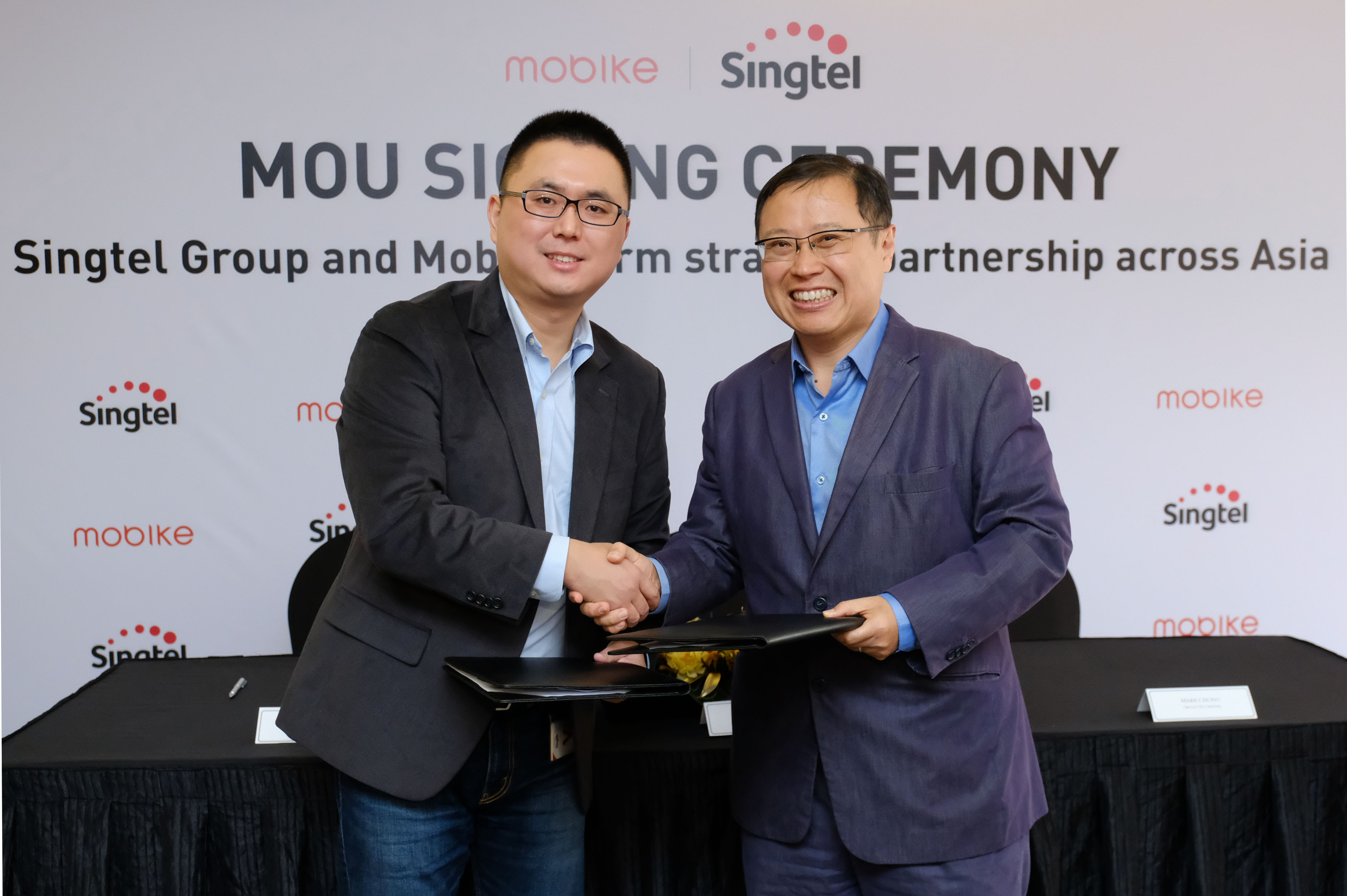 Joe Xia Mobike Co-founder and CTO and Mr Arthur Lang, CEO International Group, Singtel at MOU signing ceremony for Singtel Group-Mobike strategic partnership across Asia
