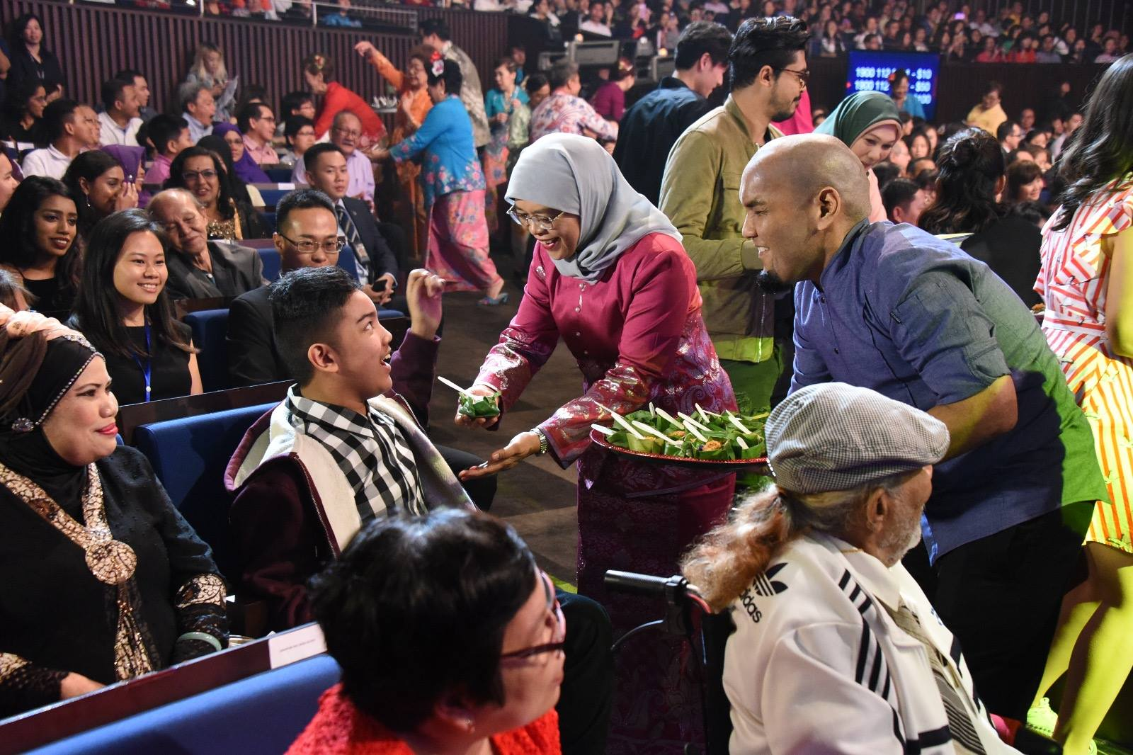 President Halimah Yacob distributing Pulut Inti (a traditional Peranakan dish)to the audience before the show.