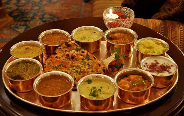 The thali is loaded with hot and spicy lentils, vegetables, sidu, which is a kind of bread and meetha bhaat (sweet rice mixed with nuts)