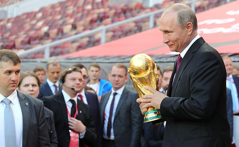 Russian president Vladimir Putin holding the FIFA World Cup Trophy at a pre-tournament ceremony in Moscow in September 2017. Photo courtesy: Wikimedia
