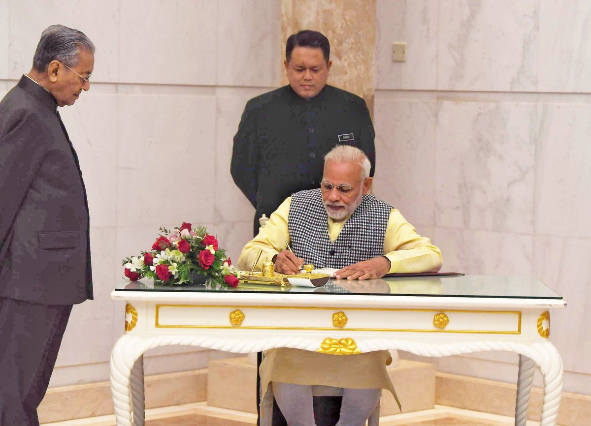 Indian Prime Minister Narendra Modi signing a document in presence of Malaysian Prime Minister Mahathir Mohammad in Kuala Lumpur.