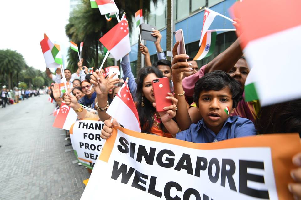 People of Indian community waving Indian and Singaporean flags to welcome Indian Prime Minister Narendra Modi.