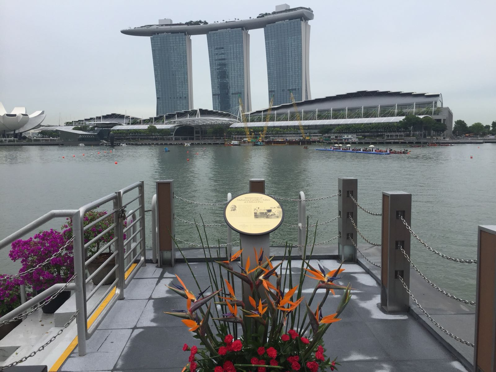 A view of Marina Bay from Clifford Pier with the board containing details about the immersion of Mahatma Gandhi's ashes  in the foreground.