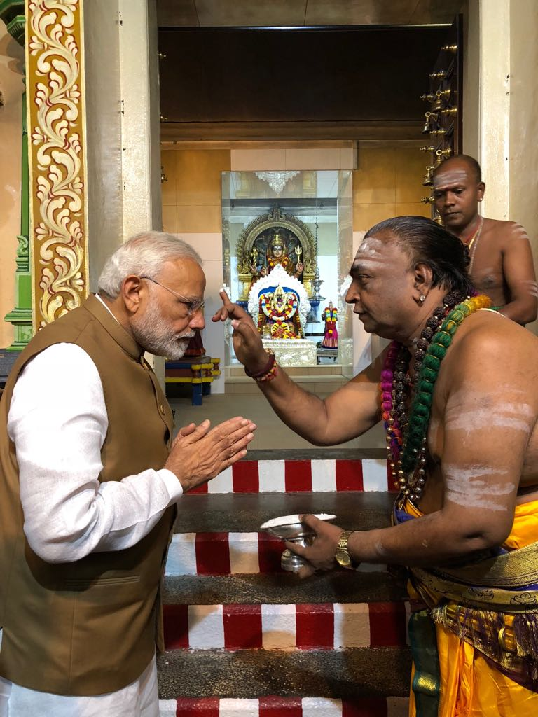 Priest applying tilak on the forehead of PM Modi during his visit to Mariamman Temple in Singapore.