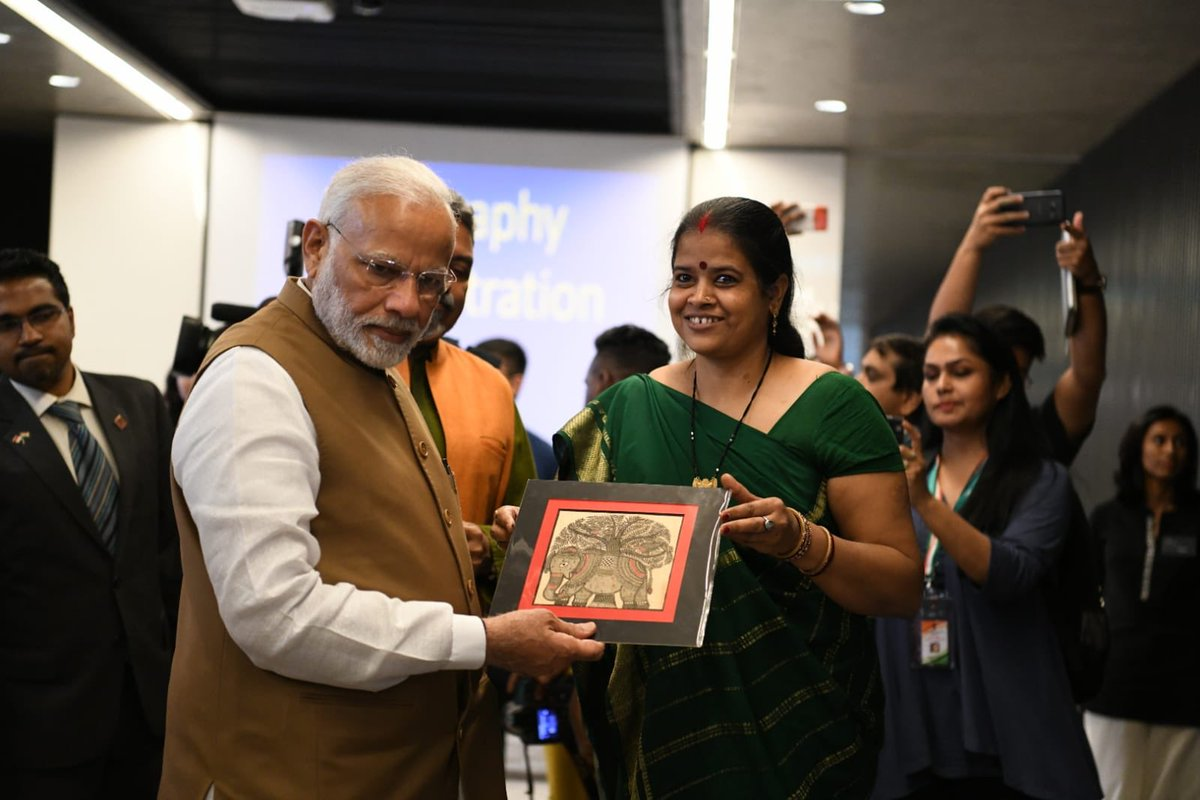 An Indian artist showing her painting to PM Modi at Indian Heritage Centre.