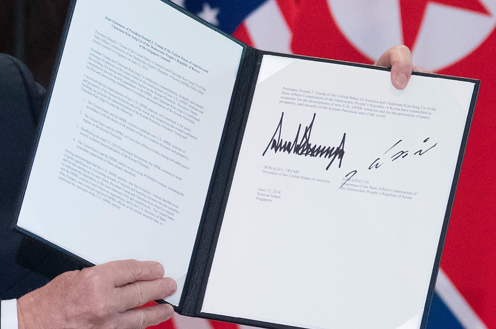 The signatures of US President Donald Trump and North Korea's leader Kim Jong Un are seen on a document following a signing ceremony during their historic US-North Korea summit. Photo courtesy: Ministry of Communications and Information