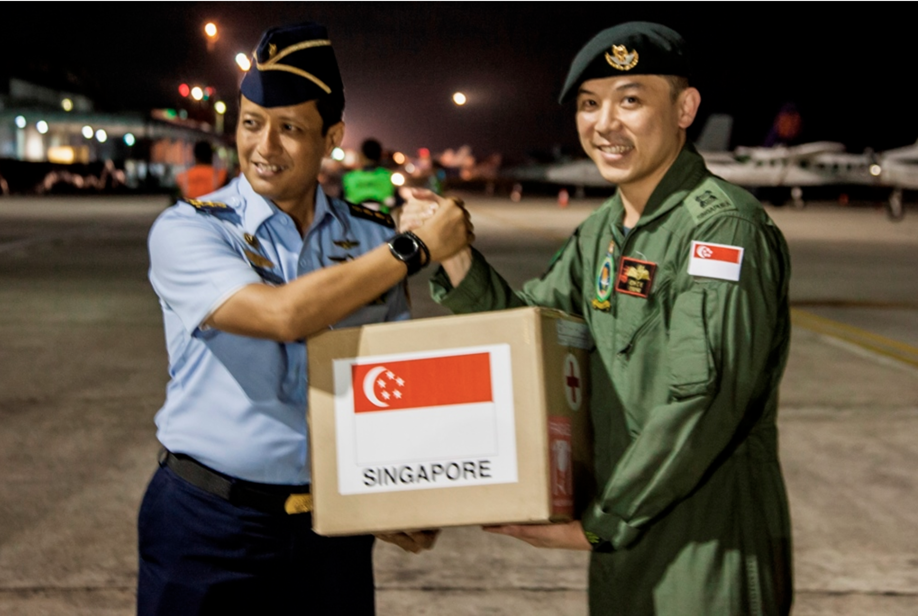 The Singapore Armed Forces Mission Commander, Lieutenant Colonel (LTC) Oh Chun Keong (right) handing over the relief package to LTC Ali Sudibyo, of the Indonesian Armed Forces (left) at Balikpapan Airport, Indonesia. Photo courtesy: Mindef