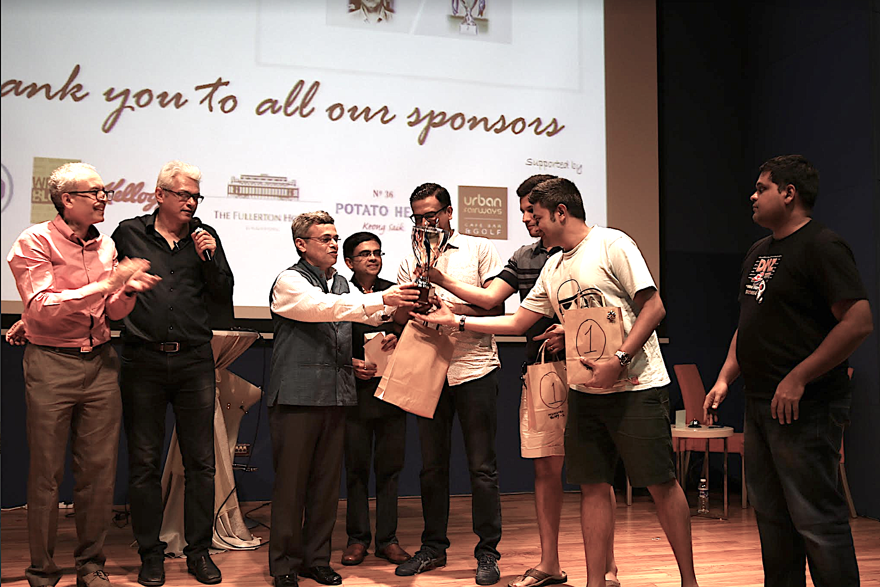 Indian High Commissioner, HE Jawed Ashraf presenting the trophy to the winning team of Mind aMaze 2017 Instant Noodles, as quizmaster Joy Bhattacharya and president of IIMPACT Saniv Aiyar (left) look on. Photo courtesy: Mind aMaze