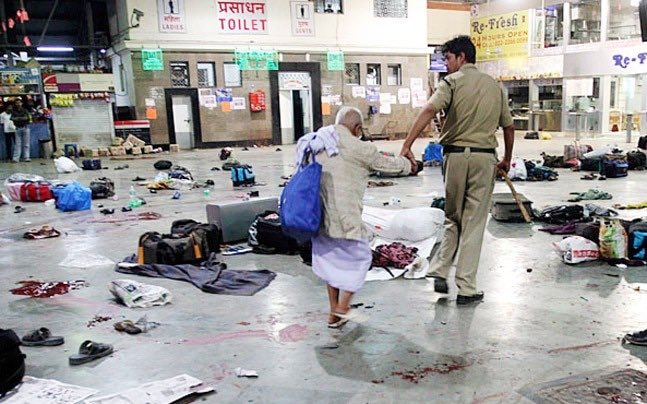 Policeman helping an old man across platform littered with victims belongings at Mumbai railway station just after the terror attack on 26 November 2008 (Photo courtesy: Daniel Carmon, Twitter