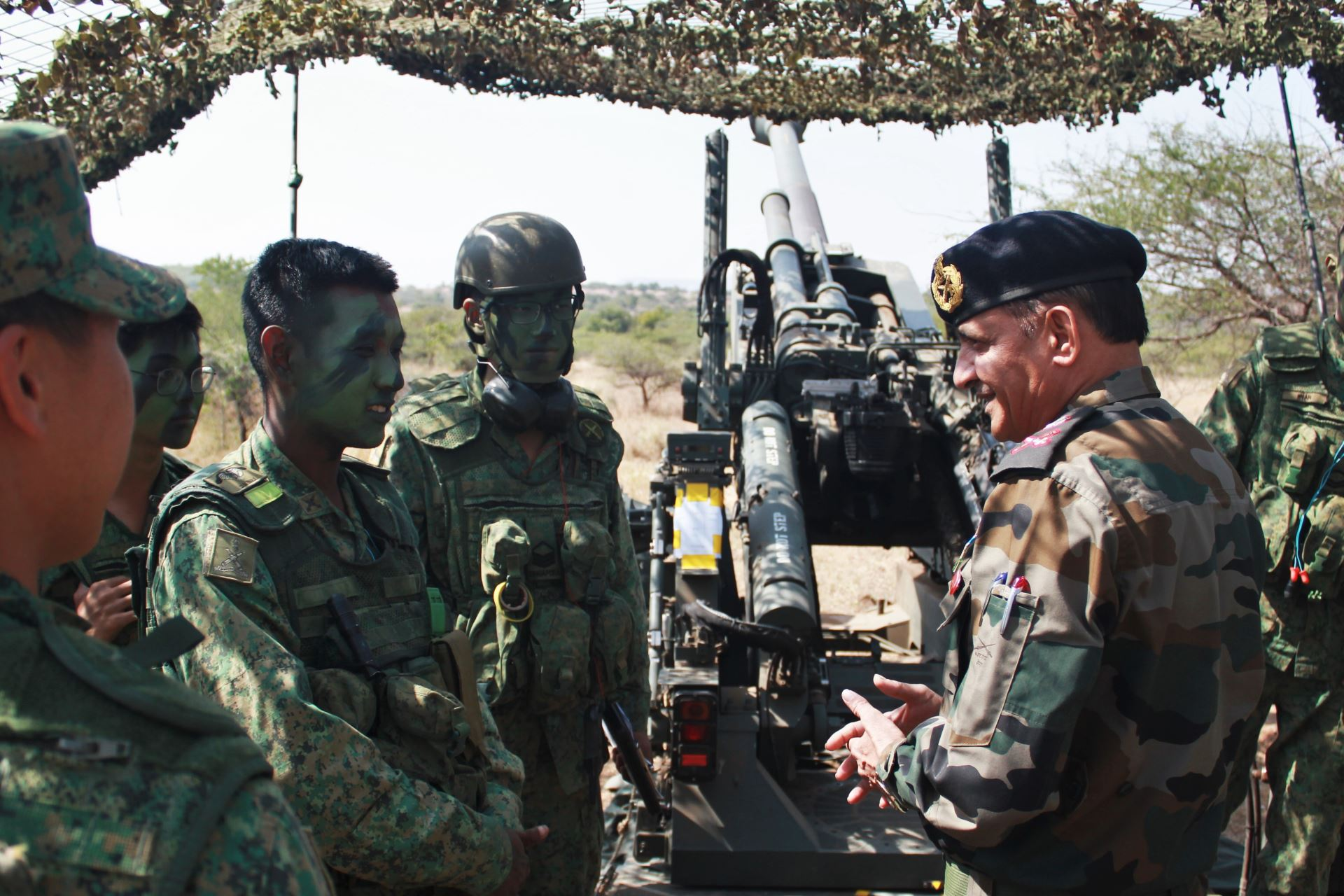 Soldiers from the Singapore Army interacting with the chief artillery instructor of the Indian Army in an informal exchange.  (Photo courtesy: Ministry of Defence, Singapore