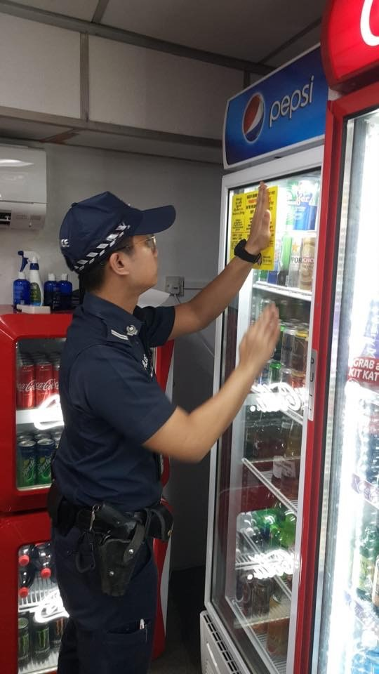 A Singapore Police Officer pasting advisory stickers at liquor outlets in Little India. Photo courtesy: Singapore Police