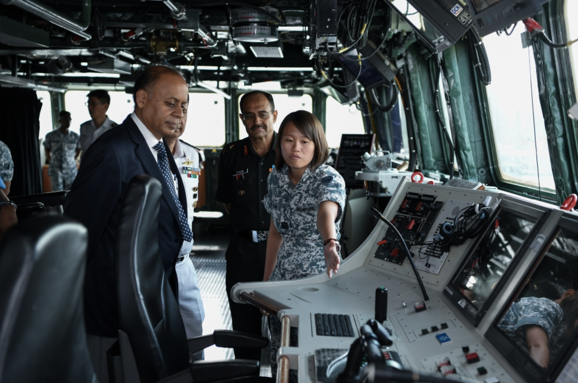 Dr Kumar receiving a brief on board the RSS Tenacious during a visit to Changi Naval Base. Photo courtesy: MINDEF
