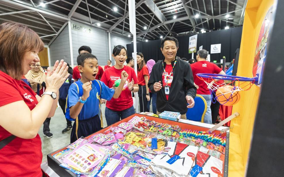 Special needs students having a ball of a time at the Singtel Carnival with Singtel staff volunteers. Photo courtesy: Singtel