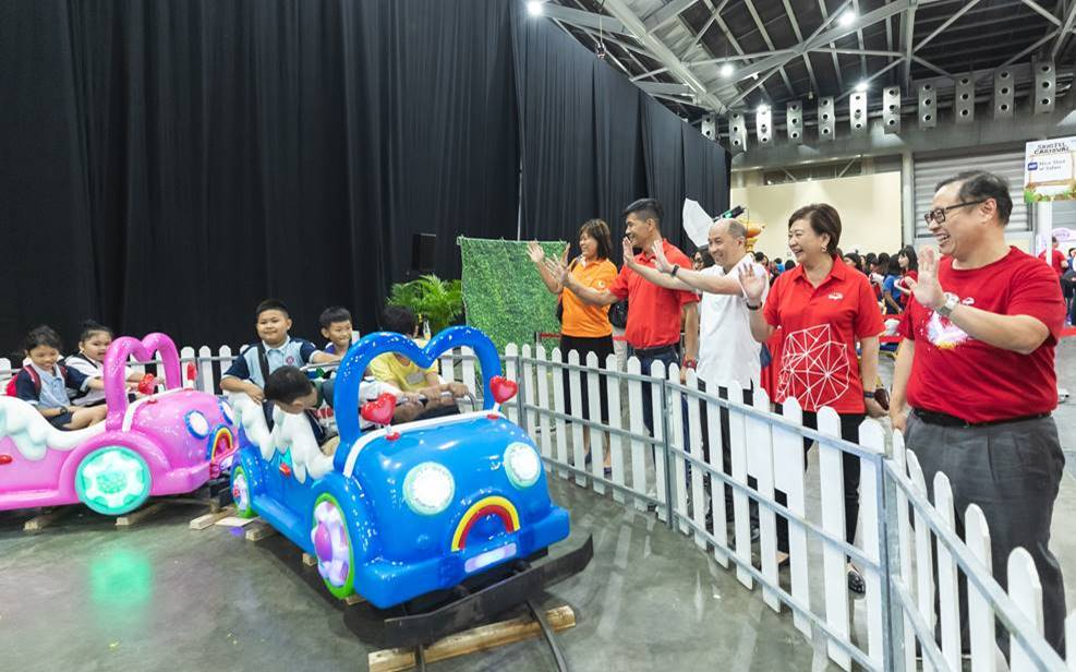 Members of Singtel's management Yuen Kuan Moon, Chairman of the STLF and CEO Consumer Singapore at Singtel (standing, third from left); Group CEO Chua Sock Koong (standing, second from right), and Arthur Lang, CEO, International (standing, first from right) waving to special needs students as they take a train ride. Photo courtesy: Singtel