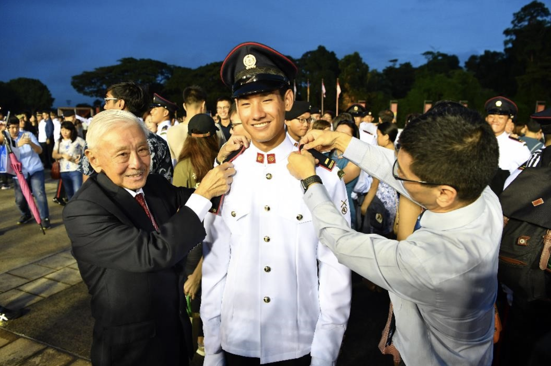 Newly-commissioned 2nd Lieutenant (2LT) Daniel Choo's grandfather LG (RET) Winston Choo and his father Warren Choo affixing the 2LT rank on to his uniform at the parade. Photo courtesy: Mindef