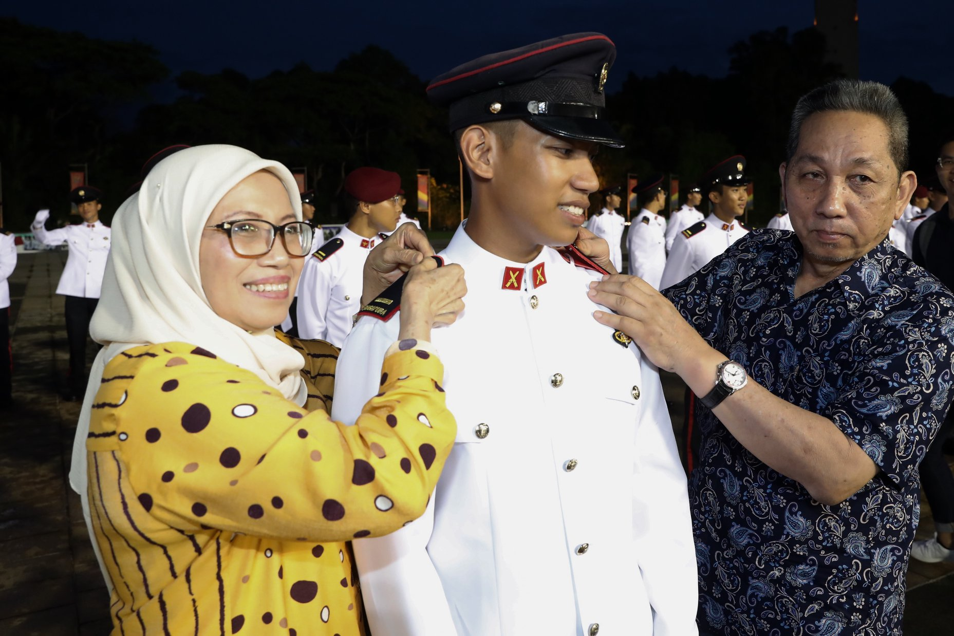 Proud parents of 2LT Muhamad Fudhail bin Abdul Latiff affixing his rank insignias on his shoulder. Photo courtesy: MCI Clement