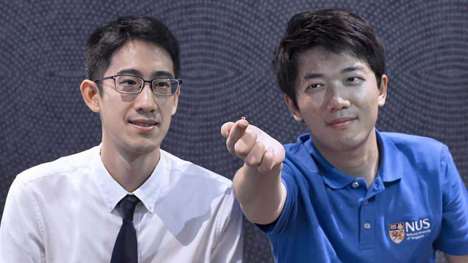 The advanced wireless technology developed by Assistant Professor John Ho (left) and doctoral student Dong Zhenya (right) can sense implantable microsensors. One of the microsensors is shown on the finger of Dong. Photo courtesy: NUS