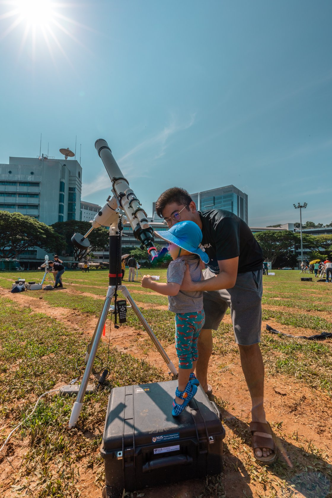 NUS School of Computing undergrad and NUS Astronomical Society President Brian Arcillas showing a young visitor how to view the sun through a telescope. Photo courtesy: NUS