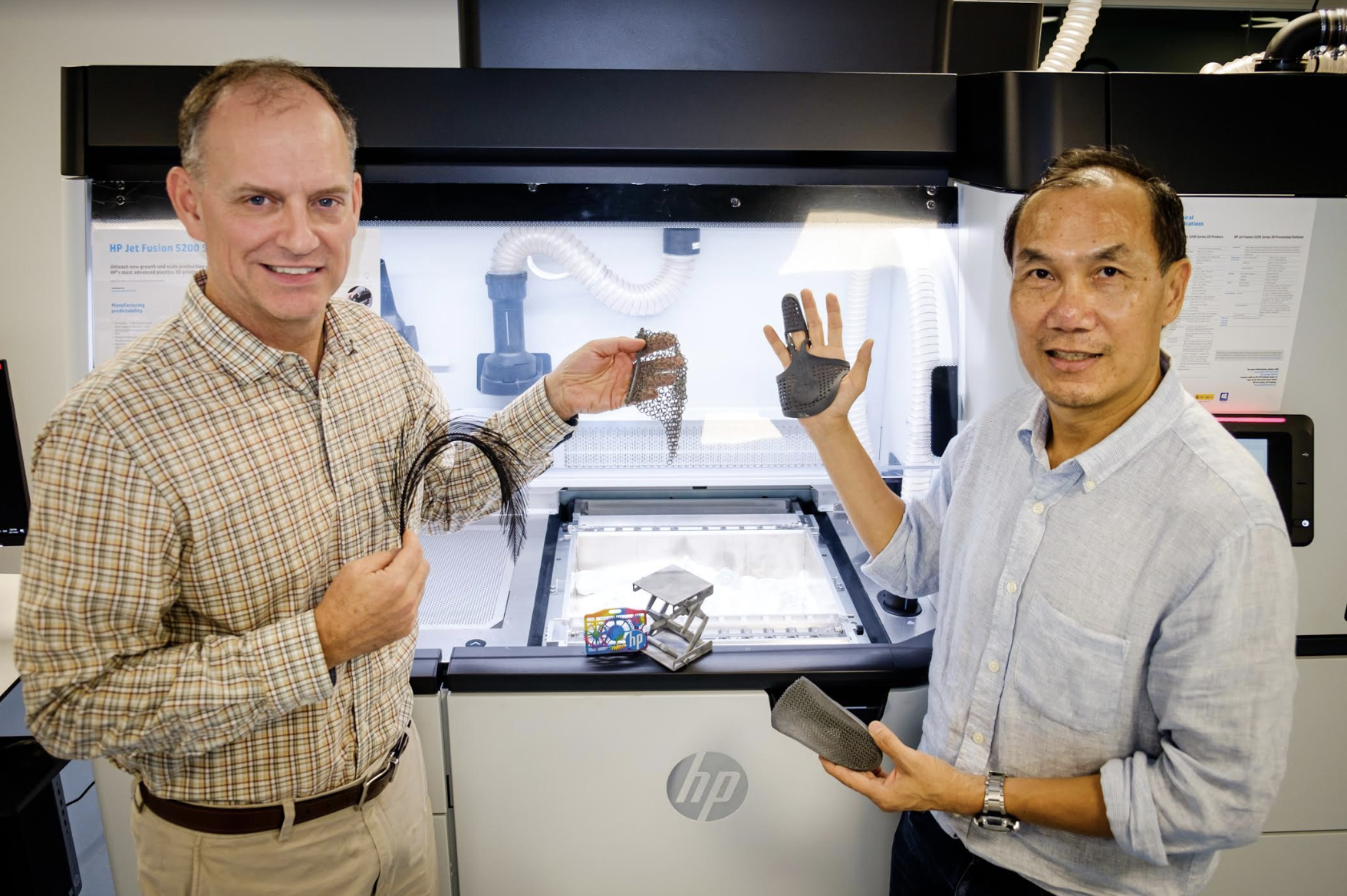 Co-directors of the HP-NTU Corporate Lab, NTU Associate Professor Tan Ming Jen (right) and Mike Reagan (left) holding up 3D-printed products from HP Jet Fusion printers which can include colour as well as print in complex shapes and with different material properties. Photo courtesy: HP