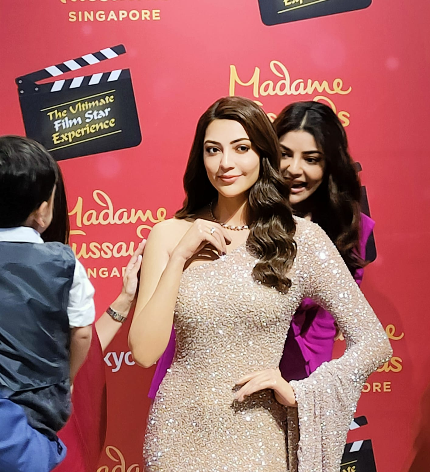 """Kajal Aggarwal plays 'Peekaboo' from behind her wax statue with her nephew who could not contain his excitement as he searched for his 'Maasi'. """"Maasi kidhar hai?' he could be heard asking many times before the unveiling. :) Photo: Connected to India"""