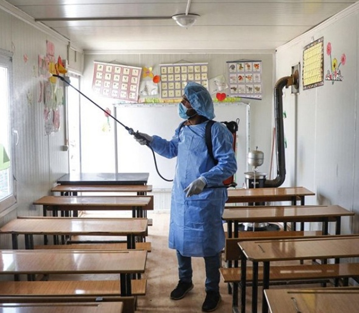 A volunteer disinfecting a make-shift classroom at a camp for displaced people in Idlib, Syria. Photo courtesy: Instagram/unicef