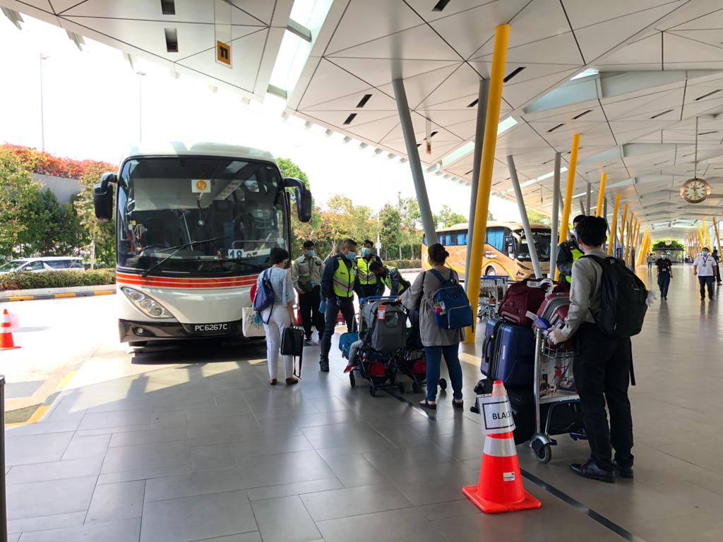Passengers boarding the bus on the way to serve their SHNs. Photo courtesy: Changi Airport