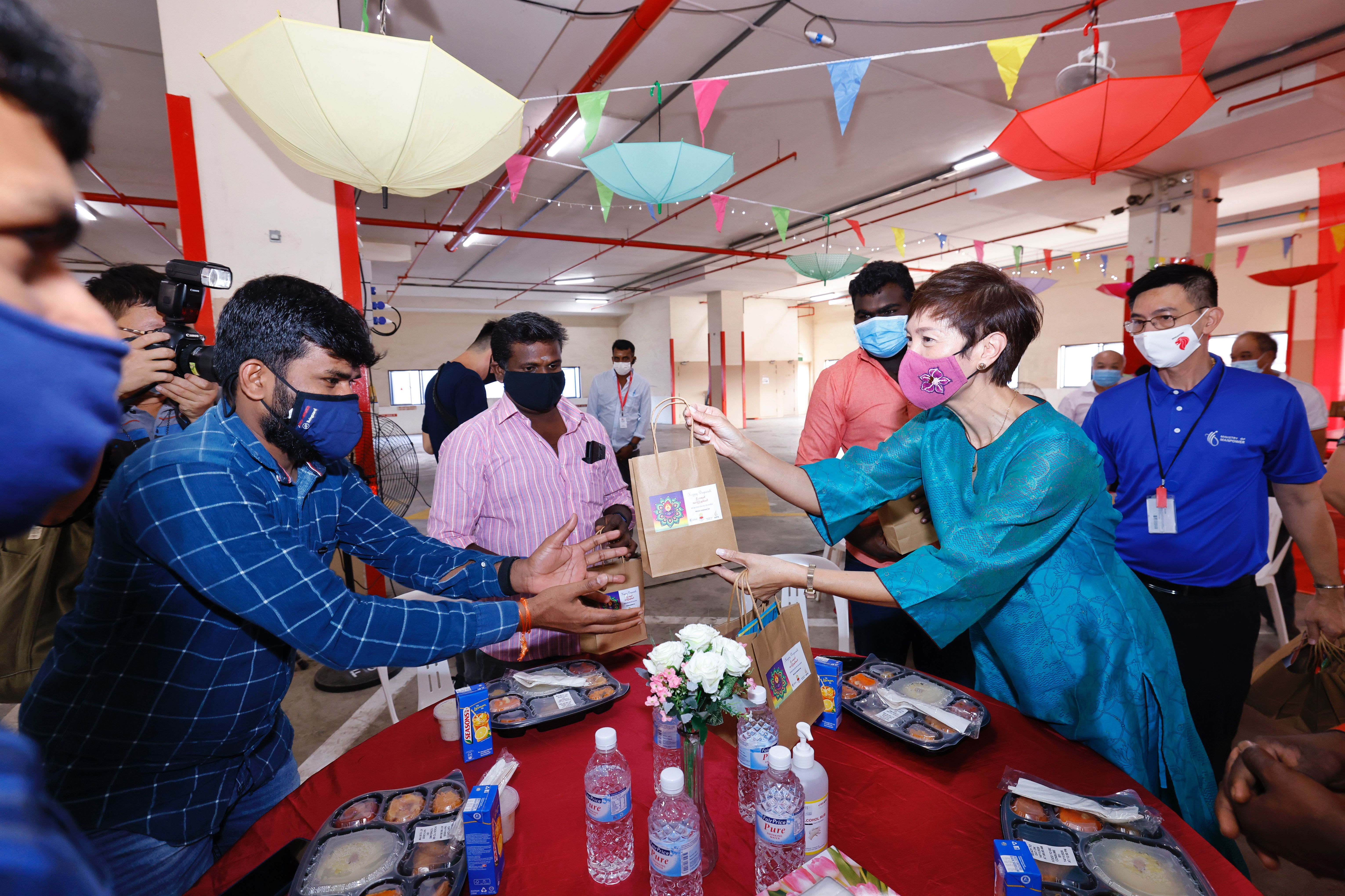 Minister for Manpower Josephine Teo handing festive treats to migrant workers. Photo courtesy: MOM