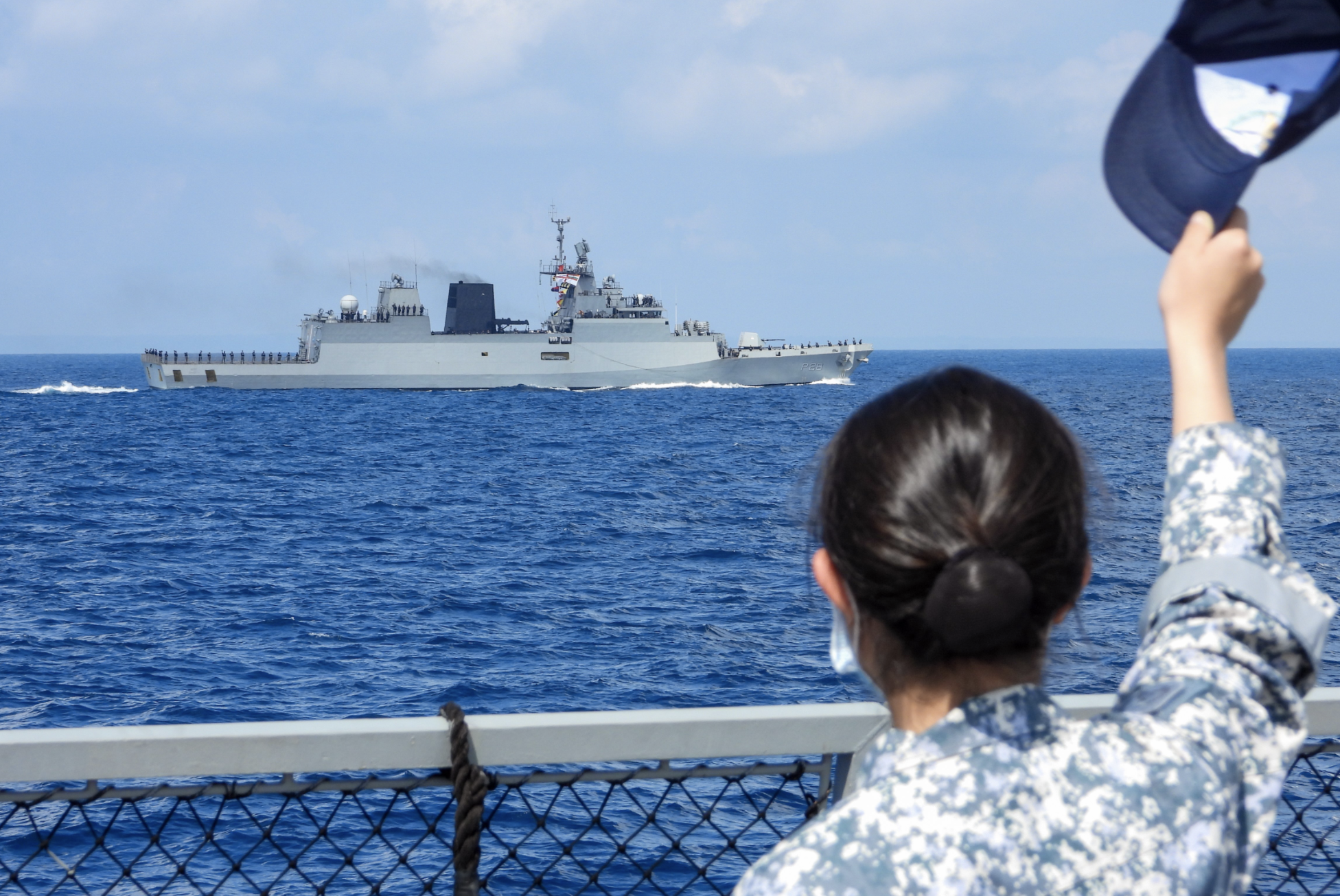 RSN sailor waving at sailors from INS Kamorta as SIMBEX 2020 concludes. Photo courtesy: Mindef